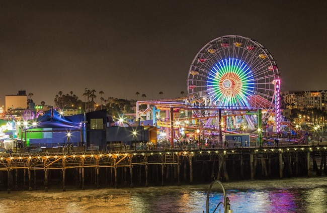 Ferris wheel and Pacific Park on Santa Monica Pier lit up at night